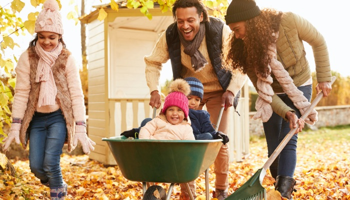 Parents In Fall Giving Children A Ride In Wheelbarrow